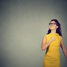 Super hero girl. Confident young woman isolated on gray wall background